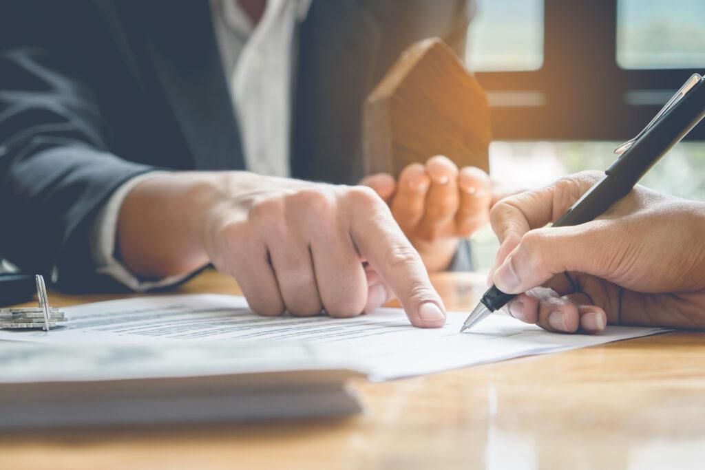 Nahaufnahme von zwei Geschäftsleuten, die die Finanzierung für ein Unternehmen unterzeichnen